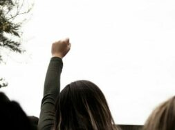 woman in gray sweater raising her left hand