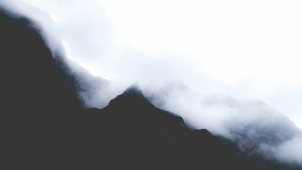 silhouette of mountain covered with fogs at daytime
