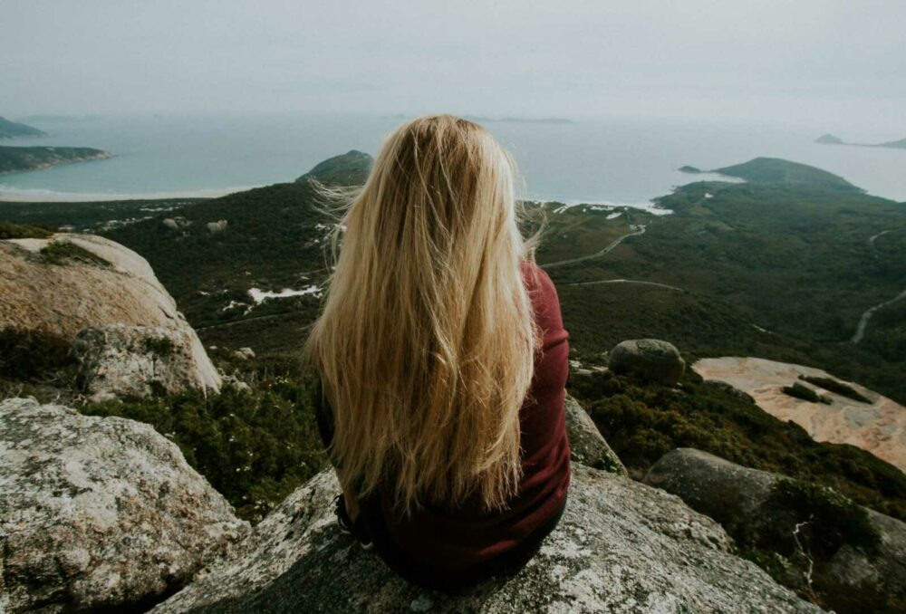 woman sitting on top mountain