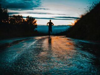 silhouette photo of a person running on road