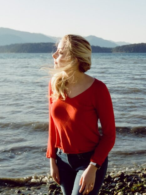 woman in red long sleeve shirt standing on rocky shore during daytime