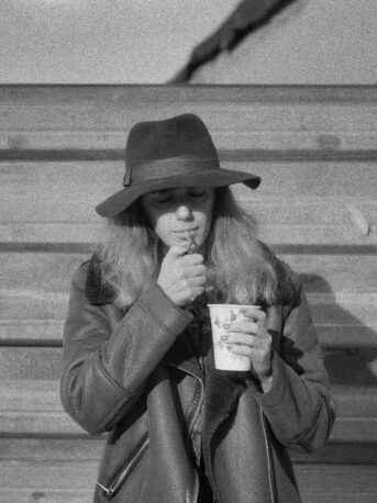 woman in coat holding cup
